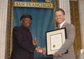 """Na ocasião, o Presidente da Câmara de San Francisco, Willie Brown (à esquerda) apresentou uma proclamação a elogiar a Igreja """"pelos seus esforços no sentido de tornar a área da baía um lugar melhor para as pessoas de todas as raças, cores, credos e estilos de vida""""."""